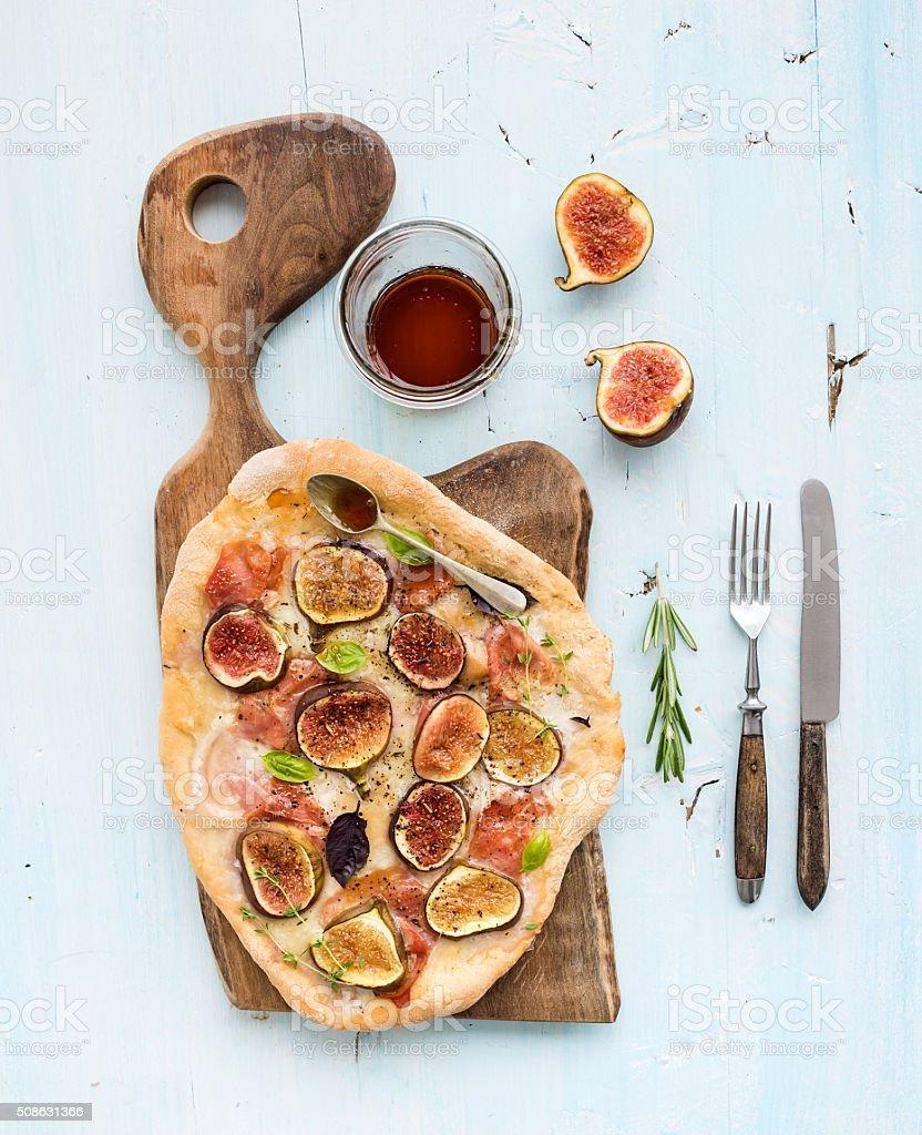 Rustic homemade pizza with figs, prosciutto and mozzarella cheese on stock photo