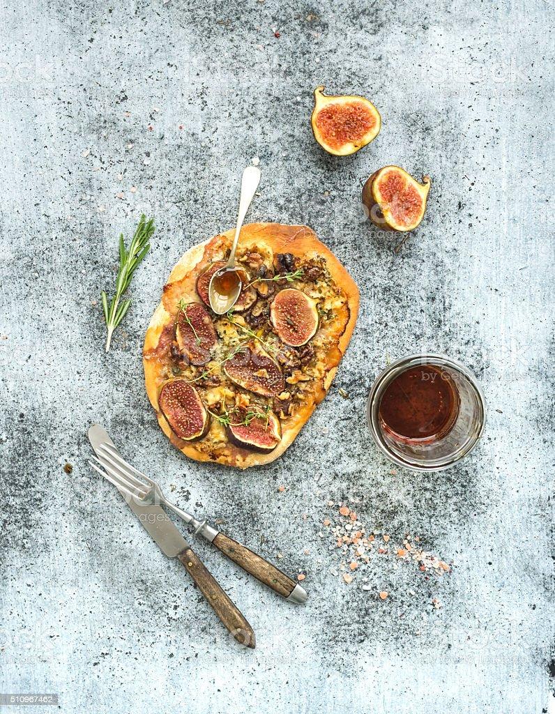Rustic homemade pizza with figs, prosciutto and mozzarella cheese over stock photo