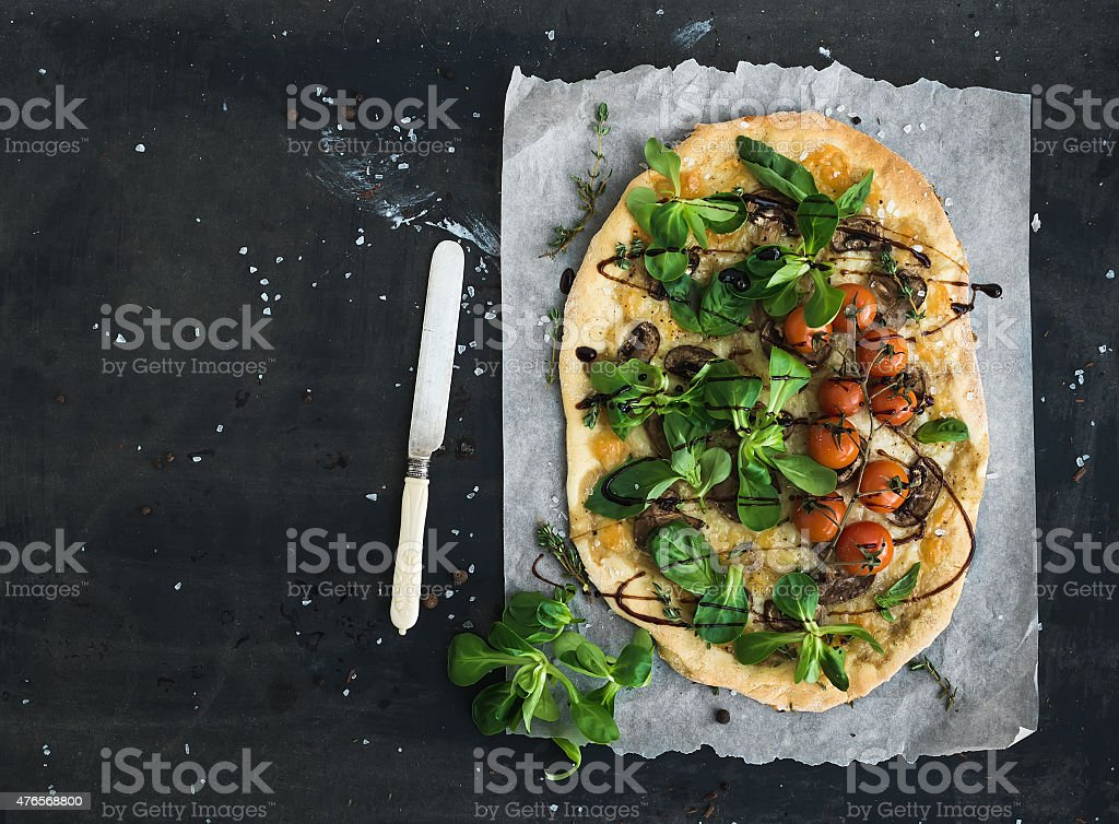 Rustic homemade pizza with fresh lamb's lettuce, mushrooms and stock photo
