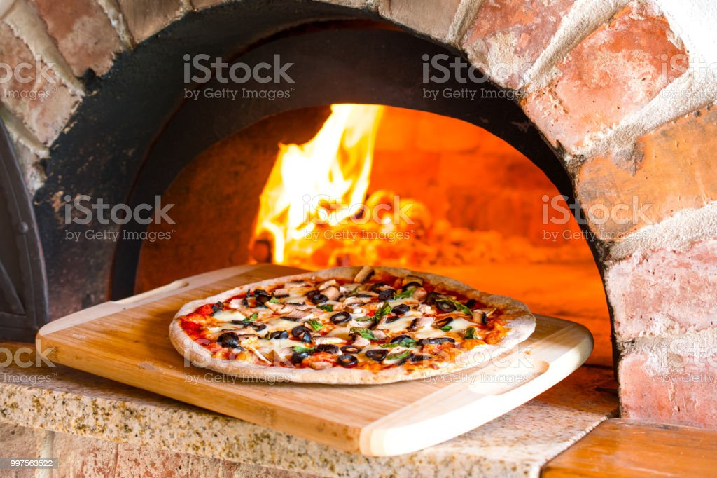 7049b1f2776285 Rustic homemade pizza with mushrooms and olives baked in a wood fired brick  oven with fire burning in the background - Stock image .