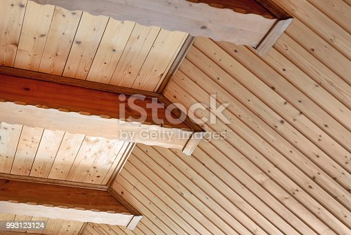 Rustic house ceiling with wide wooden beam support. Country home interior. Building natural decoration materials.