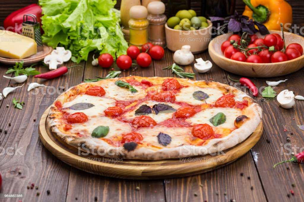 rustic italian pizza Margarita with mozzarella, cherry tomatoes and basil leaves on wooden background royalty-free stock photo