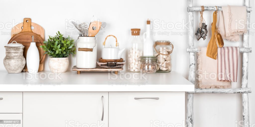Rustic kitchen bench and ladder with various utensils on white stock photo