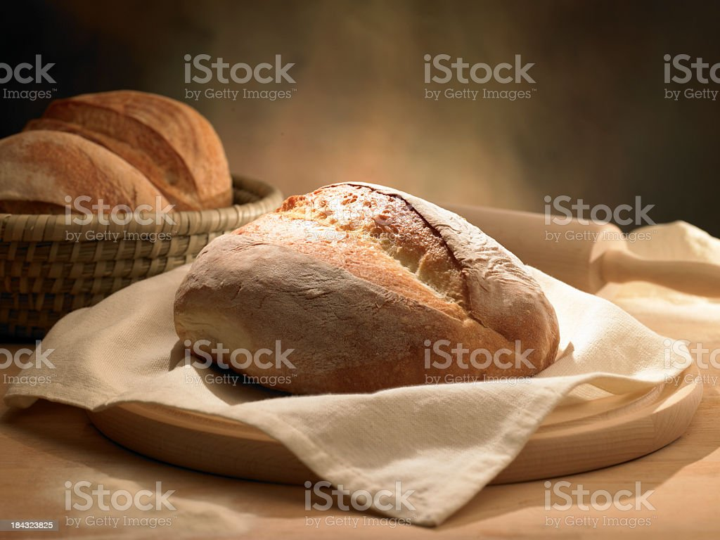 Rustic loaf of bread in cloth napkin and rolling pin royalty-free stock photo
