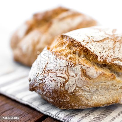 Freshly baked traditional bread on wooden table. Defocused blurry background.