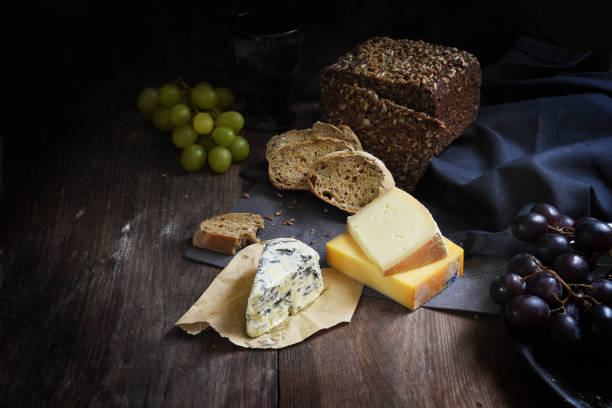 rustic meal with various cheese, wholemeal bread and grapes on a dark wooden table, copy space stock photo