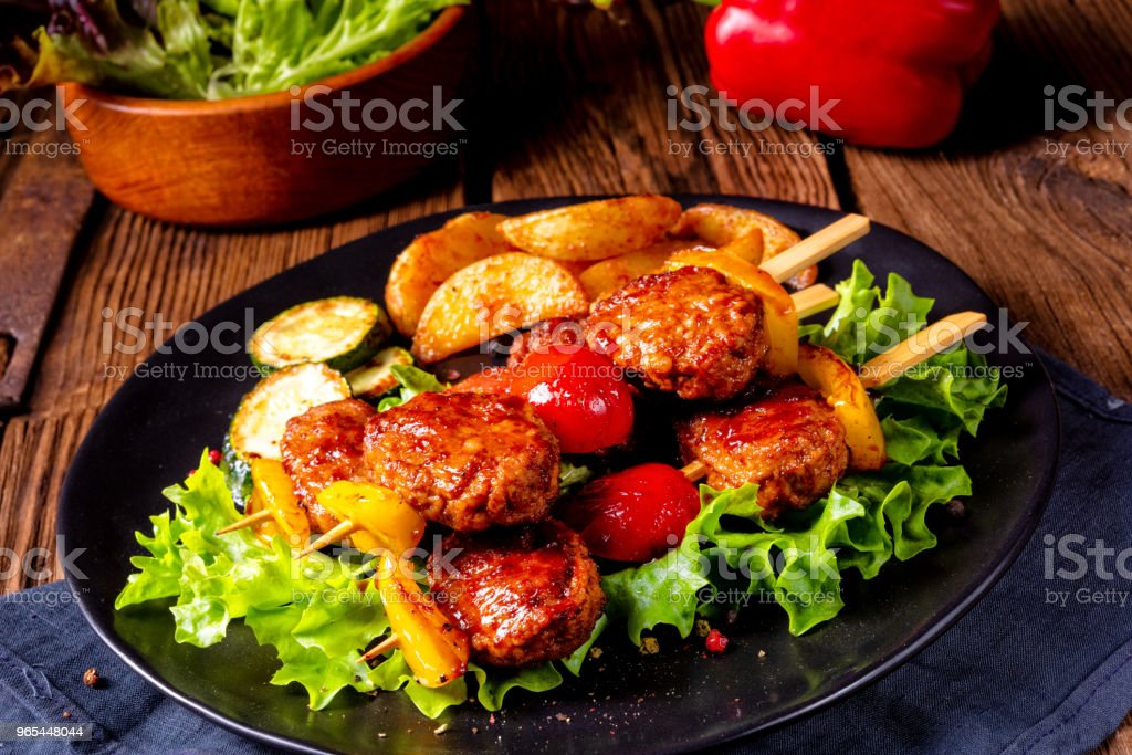 rustic Meatballs skewers of tomato, paprika and baked potato quarters royalty-free stock photo