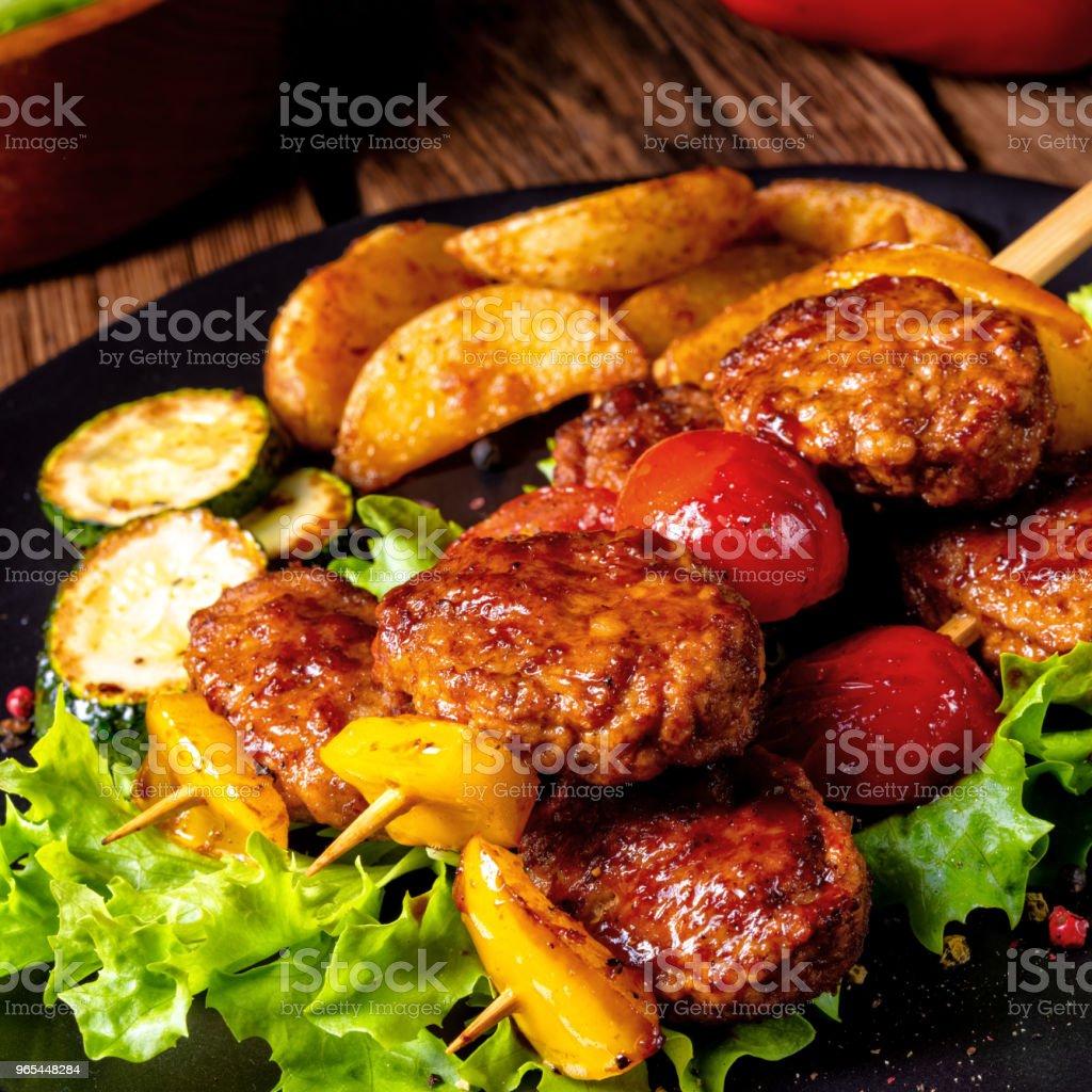 rustic Meatballs skewers of tomato, paprika and baked potato quarters zbiór zdjęć royalty-free
