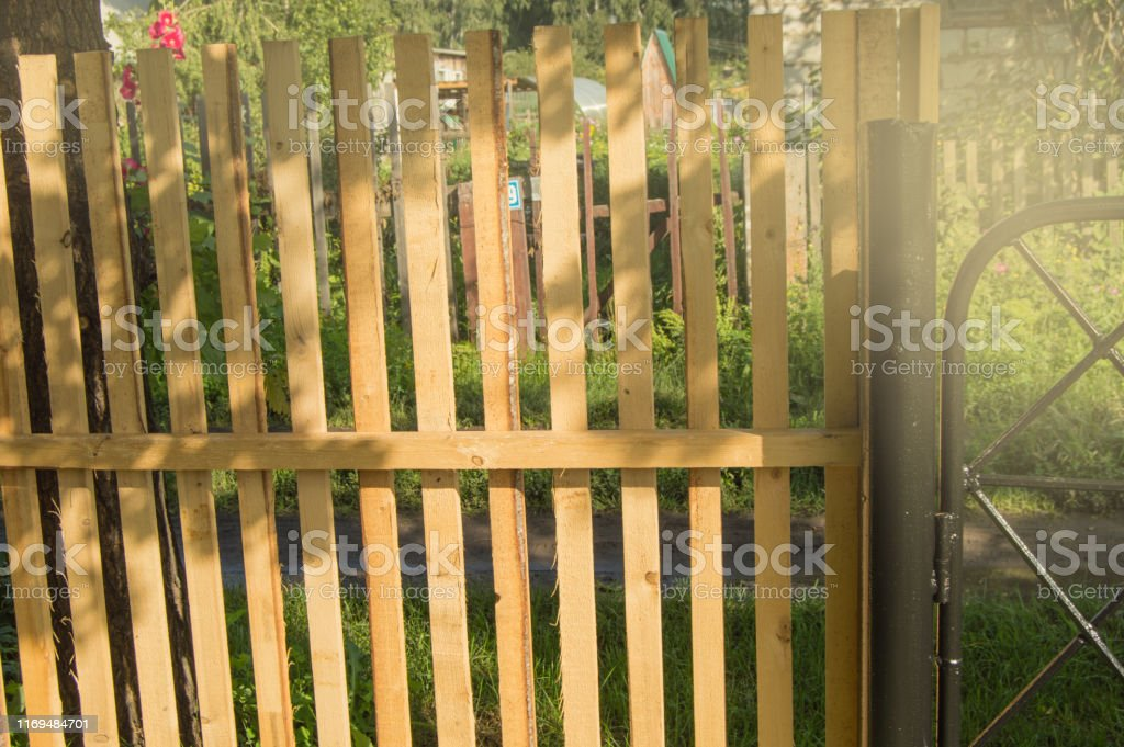 Rustic New Wooden Fence With Black Metal Posts And Gates Garden
