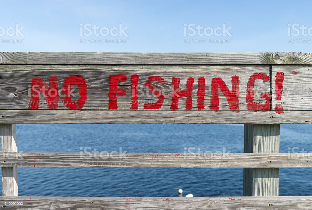 Rustic no fishing sign painted on railing stock photo