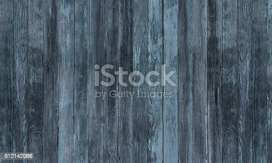 An abstract background of a rustic old weathered woodgrain fence with blue and black and gray tones.