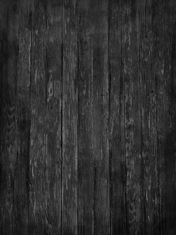 An old rustic dark monochrome black and white weathered wood grain fence abstract architecture background. Vertical orientation.