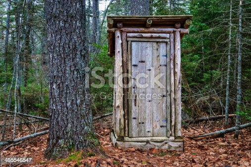 rustic outhouse in dark, coniferous Maine forest
