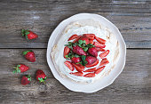 Rustic Pavlova cake with fresh strawberries and whipped cream
