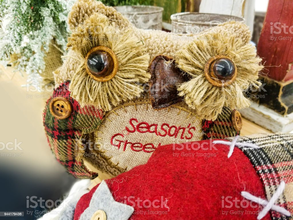 Rustic Plaid Owl Christmas Decoration with fringed eyes by Christmas tree and other country Christmas objects stock photo