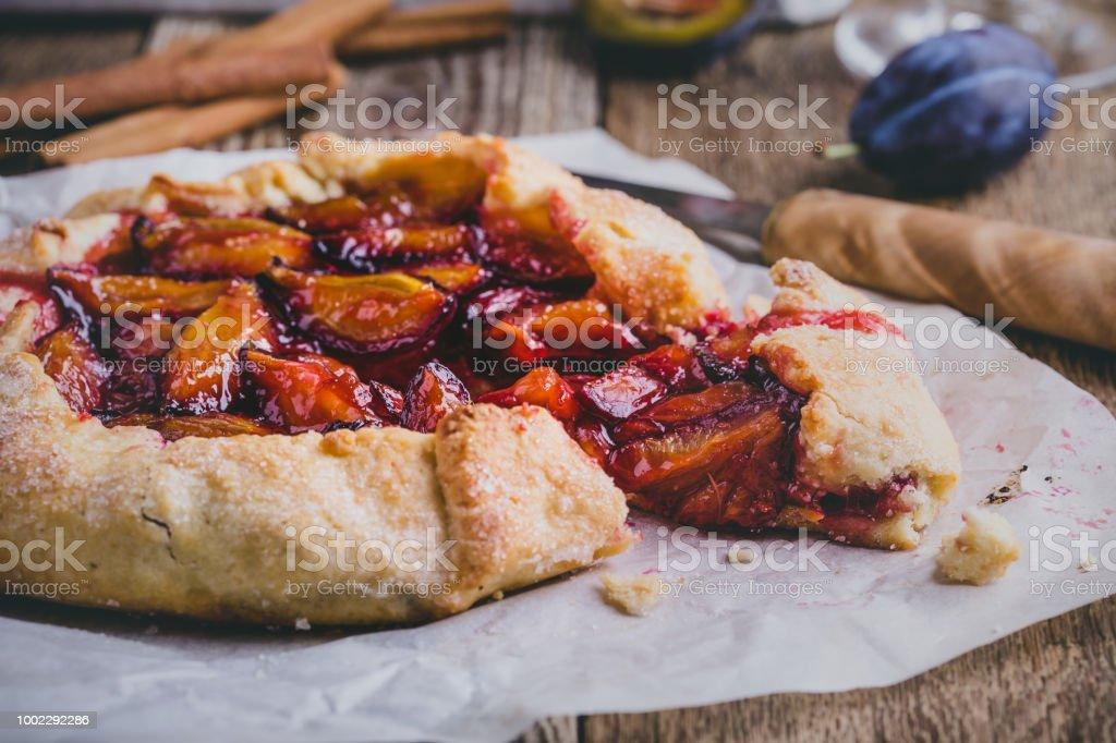 Rustic plum tart on wooden background stock photo