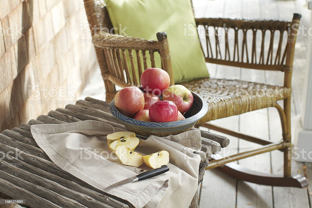 Rustic porch with apples and rocking chair royalty-free stock photo