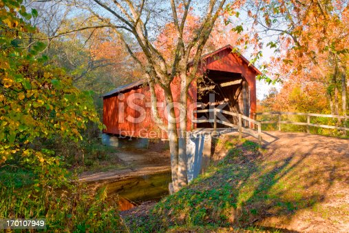 red covered bridge across stream with early autumn color, in Missouri