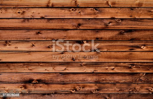 A full frame abstract background image of red and black color rustic textured boards with knotted wood grain of a barn exterior.
