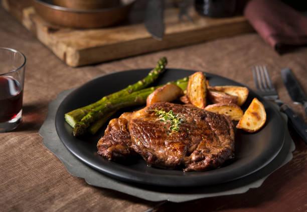 rustikale ribeye-steak-dinner - steak anbraten stock-fotos und bilder