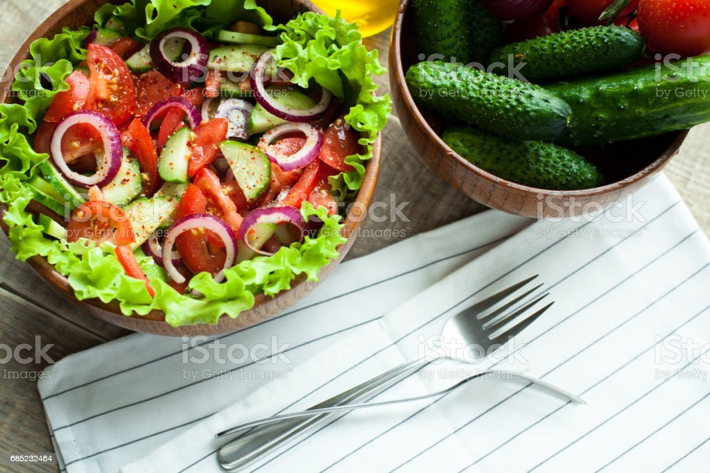 Rustic salad of fresh tomatoes, cucumbers, red onions and lettuce, dressed with olive oil and ground pepper in a wooden bowl. Top view royalty-free stock photo