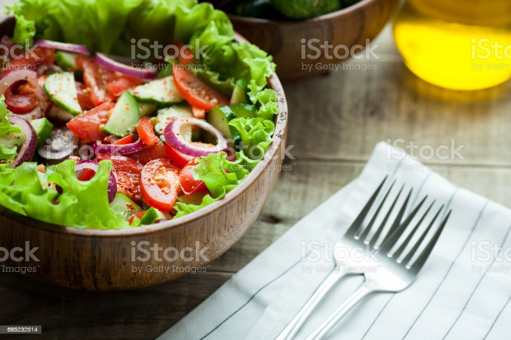 Rustic salad of fresh tomatoes, cucumbers, red onions and lettuce, dressed with olive oil and ground pepper in a wooden bowl. Top view foto de stock royalty-free