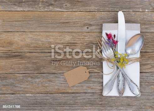 Table place setting with silver cutlery and flowers on wooden table.