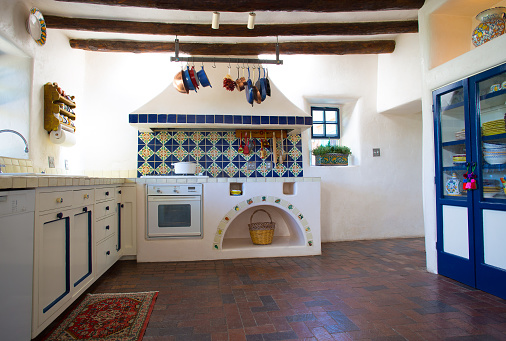 Rustic Southwest USA Kitchen: Old-fashioned brick floor, ceiling beams, counters, drawers, oven. Wide angle. Shot in Santa Fe, NM.