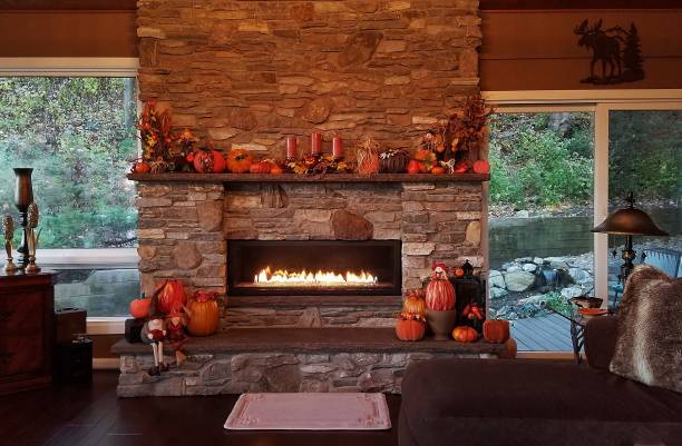 Rustic Stone Fireplace, Flames Glowing, During the Daytime of the Autumn Holiday Season stock photo