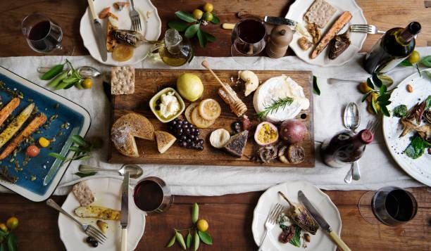 cena al estilo rústico con tabla de quesos - comida francesa fotografías e imágenes de stock