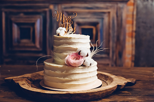 Rustic style wedding cake with cotton and floral decoration.
