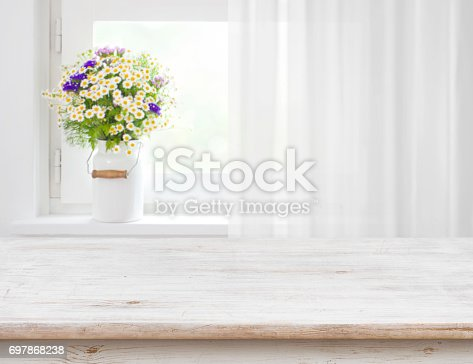 istock Rustic table in front of wild flowers on wooden window 697868238