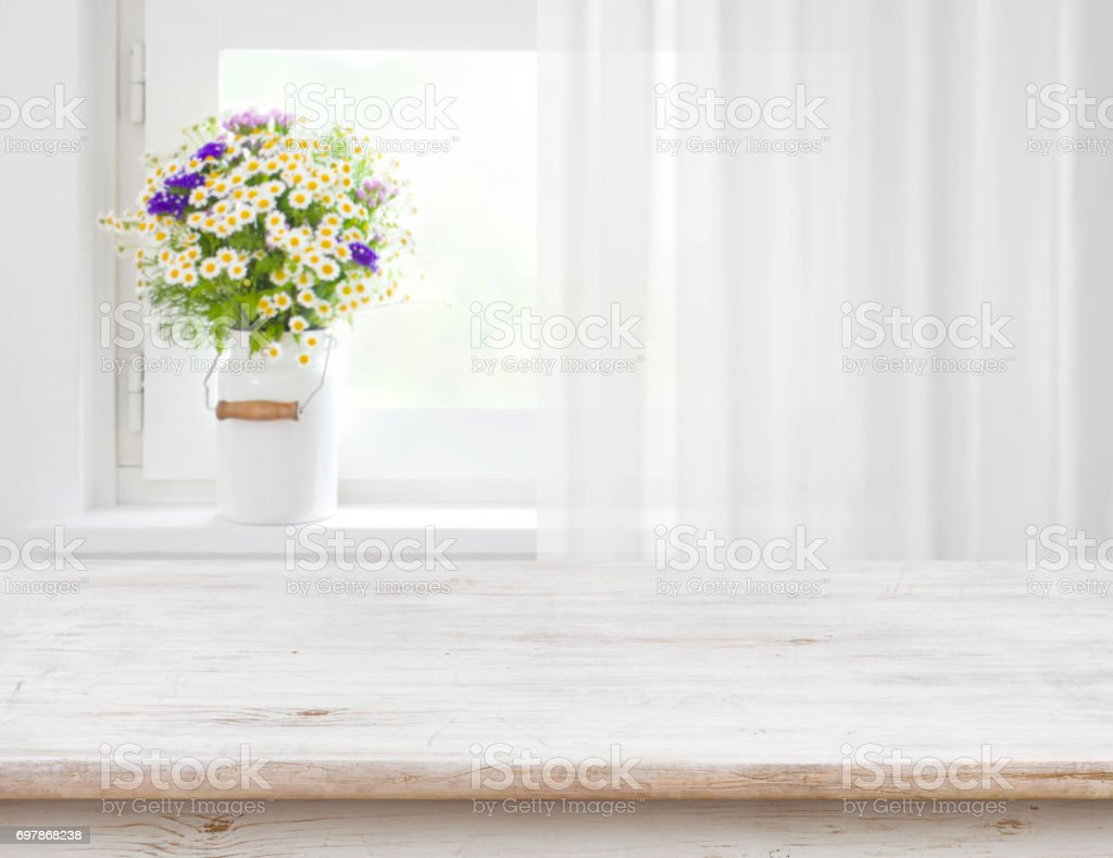 Rustic table in front of wild flowers on wooden window stock photo