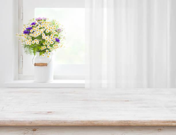 rustikaler tisch vor wilden blumen auf holzfenster - gardinen weiß stock-fotos und bilder