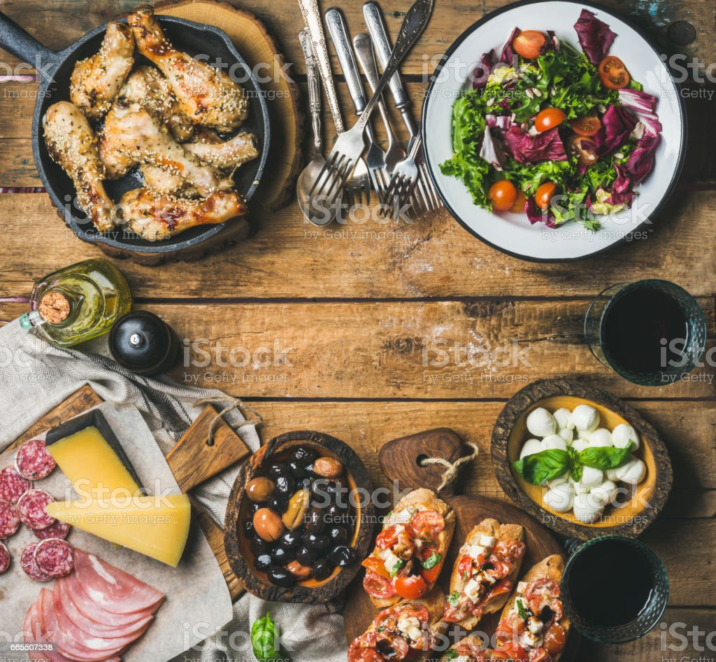 Rustic table set with meat, cheese, snacks, wine, copy space stock photo