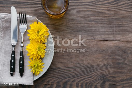 istock Rustic table setting with linen napkin, cutlery, ceramic plates, yellow glasses and yellow flowers 1051954214