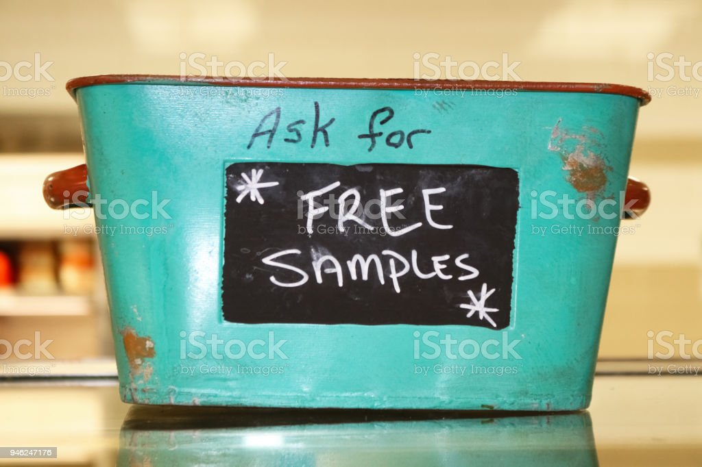 Rustic tin basket sitting on counter that says Ask for free samples stock photo