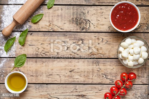 istock Rustic traditional Italian food background with empty copy design space on aged wooden texture table. Basil, olive oil, tomato sauce, rolling pin, tomatoes. 670702146