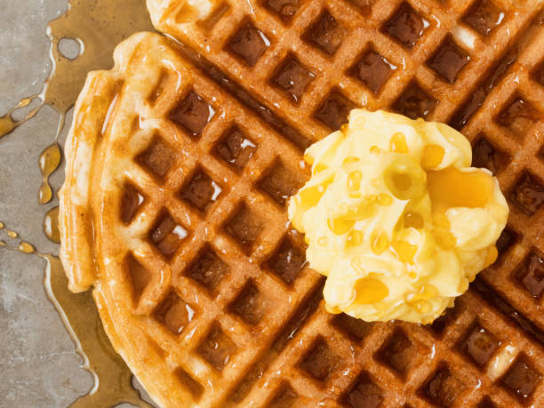 rustic traditional waffle with butter and maple syrup close up of rustic traditional waffle with butter and maple syrup waffle stock pictures, royalty-free photos & images