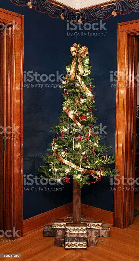Rustic Victorian Alpine Christmas Tree In Corner Stock Photo