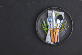 Rustic vintage set of cutlery knife, fork and spoon in black ceramic plate