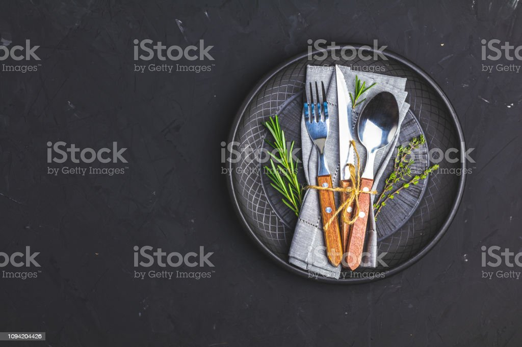 Rustic vintage set of cutlery knife, fork and spoon in black ceramic plate stock photo
