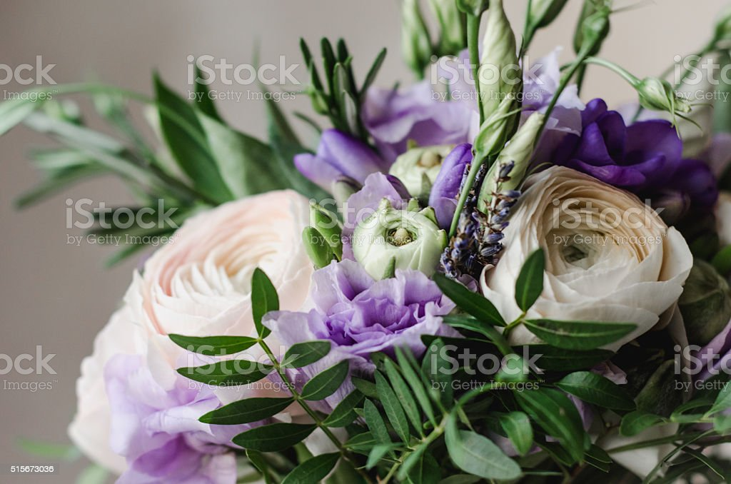Rustic wedding bouquet of violet ranunculus, lavender flowers, white background stock photo