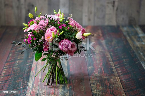 istock Rustic wedding bouquet with pink roses and Lisianthus flowers. 530922612