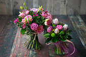 Rustic wedding bouquets with pink roses, carnations, daisies, and tulips.
