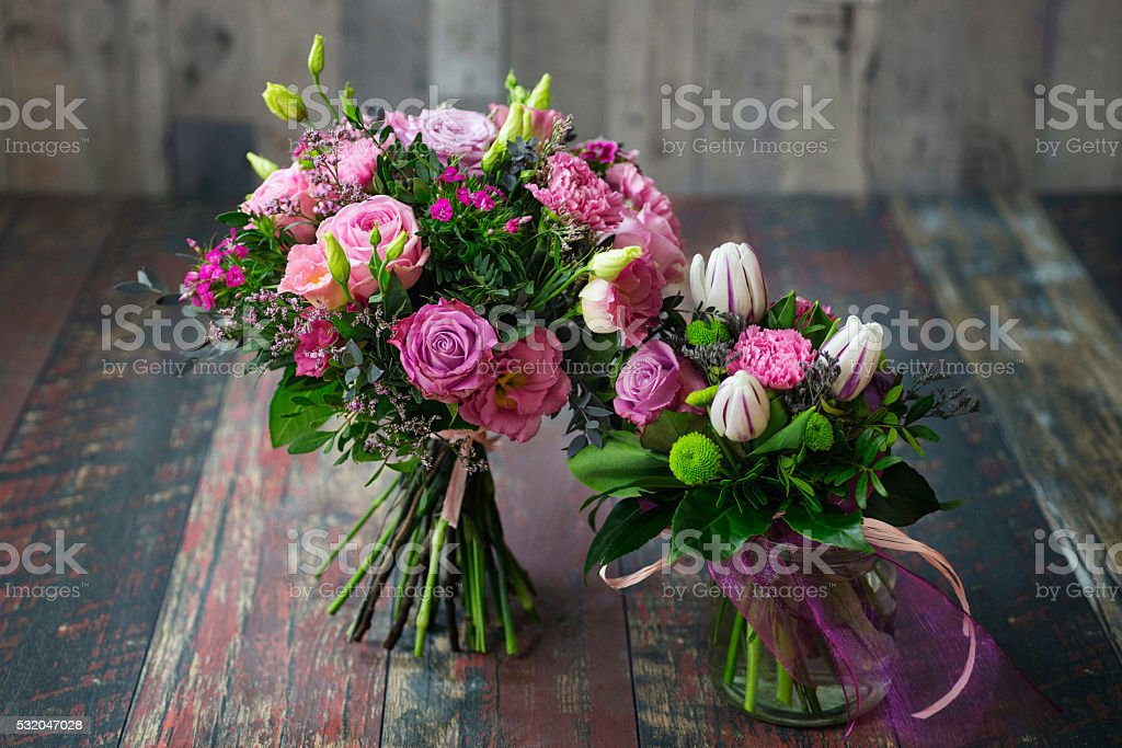 Rustic wedding bouquets with pink roses, carnations, daisies, and tulips. stock photo