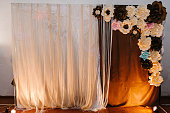 Rustic wedding photo zone with flowers. Hand made wedding decorations includes Photo Booth. Place for taking pictures, photograph.
