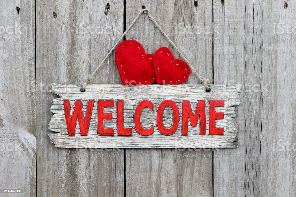 Rustic welcome sign with two red hearts hanging on door stock photo