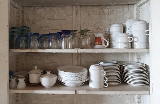 rustikale weiß schrank ausgestattet mit weißen teller, gläser, tassen und untertassen - küchenorganisation stock-fotos und bilder