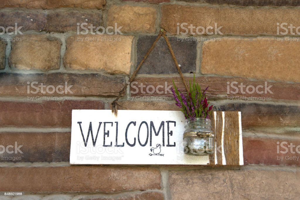 Rustic white wood welcome sign hanging on brick wall stock photo